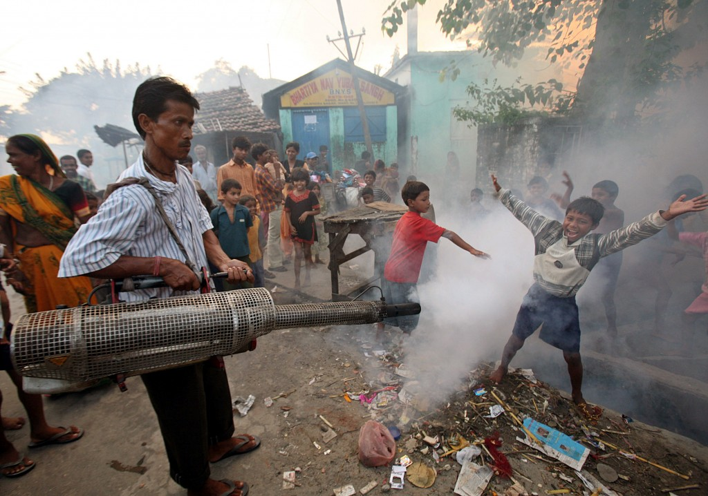 Children play in the fumes of a municipality fumigant sprayer in a slum area in the northeastern Indian city of Siliguri October 5, 2006. Photo by Rupak De Chowdhuri/Reuters