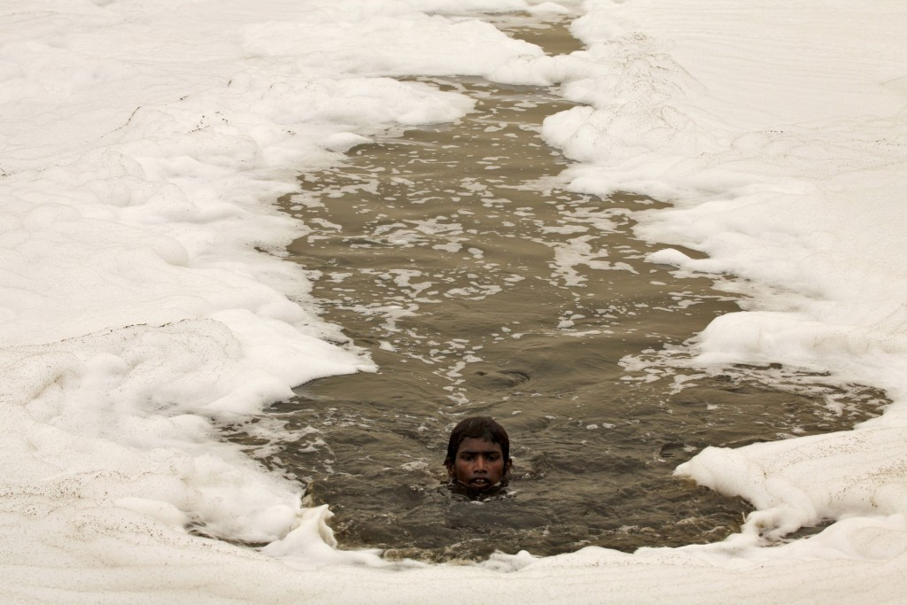 A boy swims in the polluted water of the Yamuna River to dive for offerings thrown in by worshippers amidst a dust haze in New Delhi during World Environment Day in 2010. Photo by Reinhard Krause/Reuters