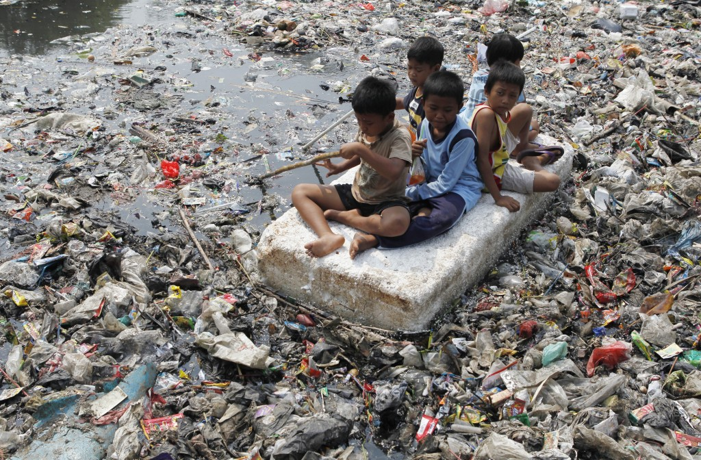 Children sitting on a makeshift raft play in a river full of rubbish in a slum area of Jakarta in 2012. Photo by Enny Nuraheni/Reuters