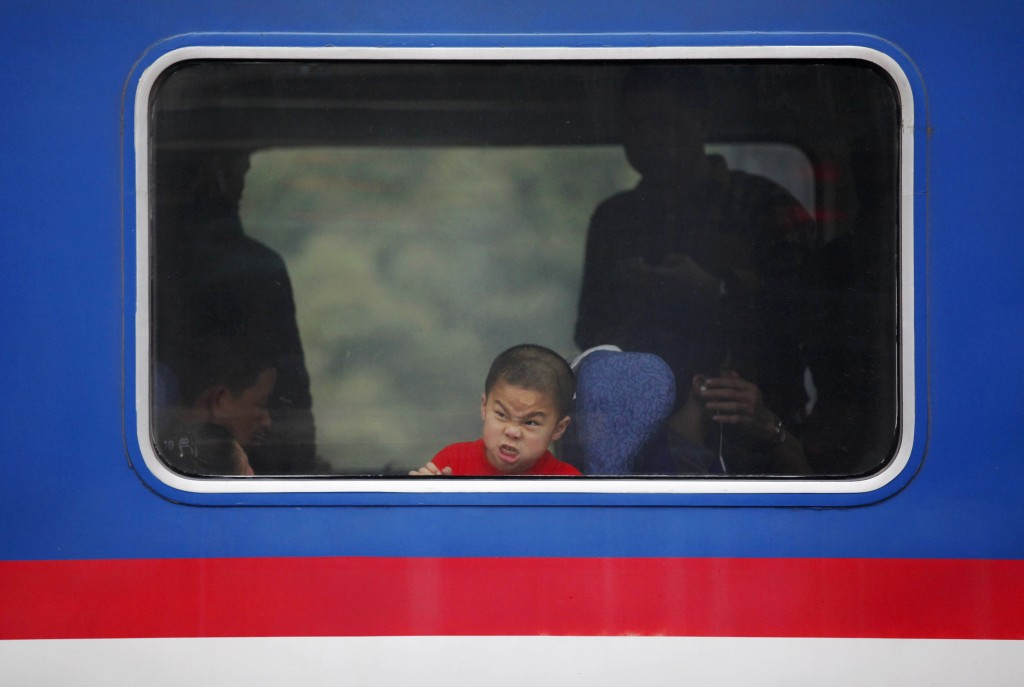 A boy makes faces as he looks out a window of a train at a railway station in Huizhou, Guangdong province Feb. 11. Photo by Reuters