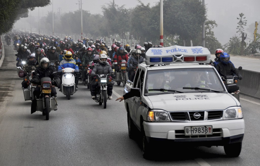 A police car leads a parade of migrant workers who ride their motorcycles to go home for the Spring Festival, in Fengkai county, Guangdong province, Feb. 12. Photo by China Daily via Reuters