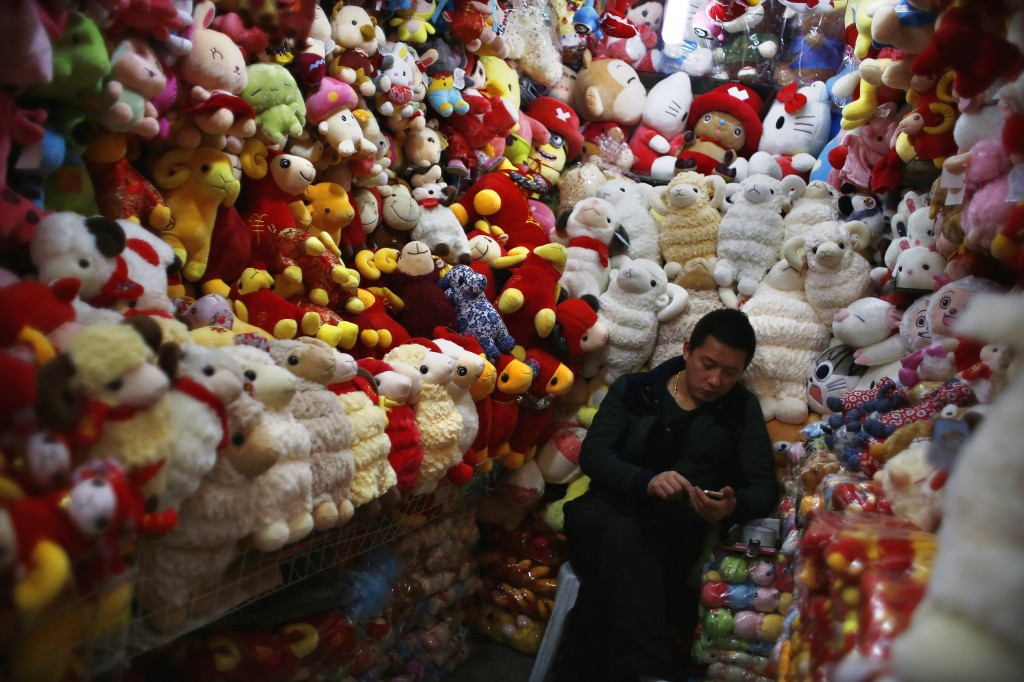 A vendor, selling traditional decorations for the upcoming Chinese Lunar New Year, waits for customers at a shopping area in downtown Shanghai on Feb. 12. Photo by Carlos Barria/Reuters