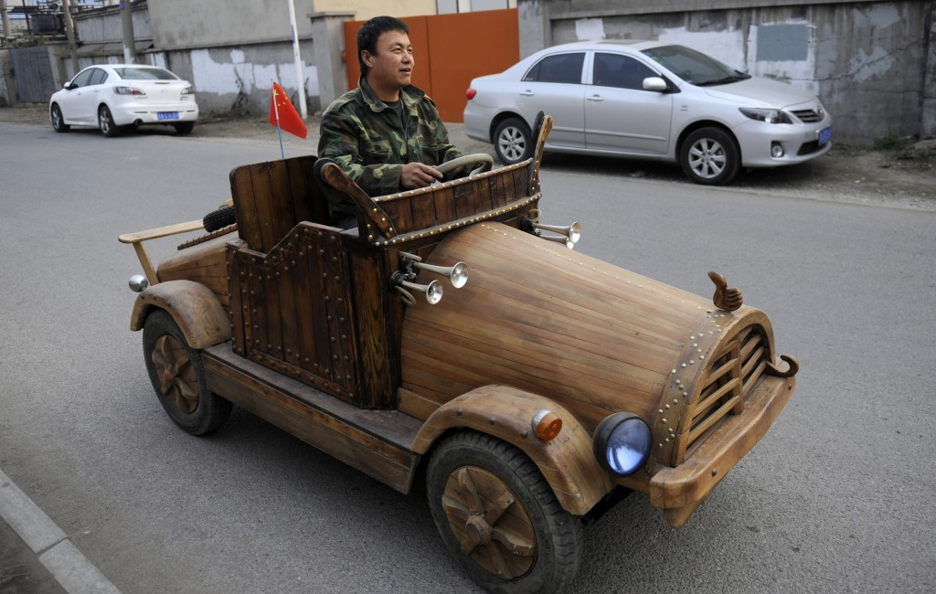 Liu Fulong takes his homemade wooden electronic vehicle for a drive in Shenyang, Liaoning province. The wood car weighs more than 400 pounds and can drive up to nearly 20 miles per hour, according to Chinese media. Photo by Reuters/China Daily.