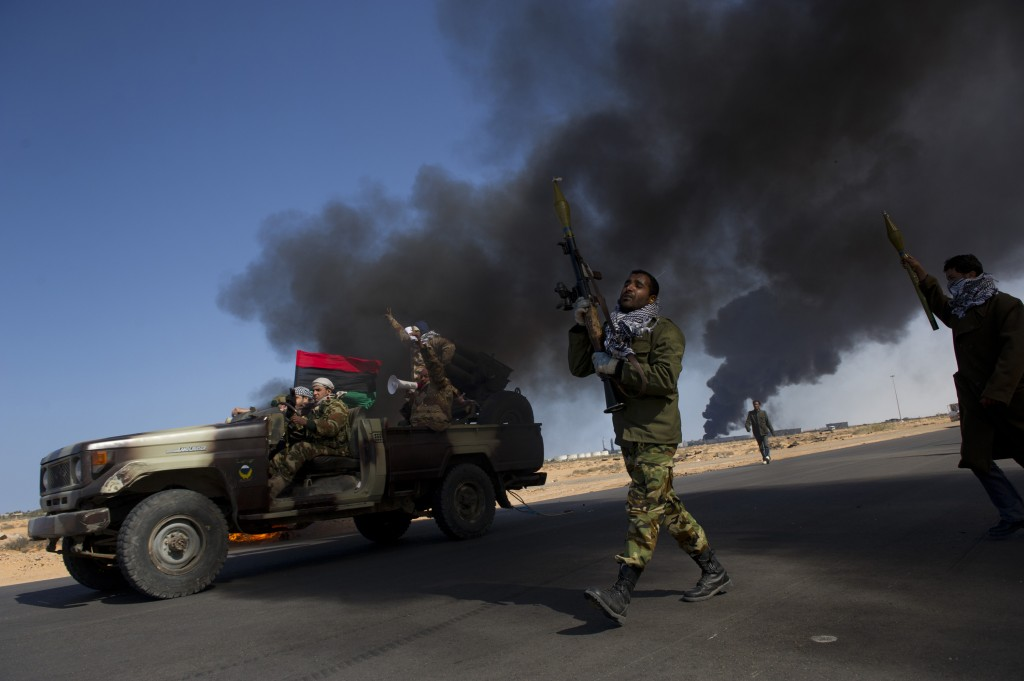 Opposition troops burn tires to use as cover during heavy fighting, shelling and airstrikes near the main checkpoint close to the refinery in Ras Lanuf, as rebel troops pull back in Eastern Libya, March 11, 2011. Photo by Lynsey Addario for The New York Times