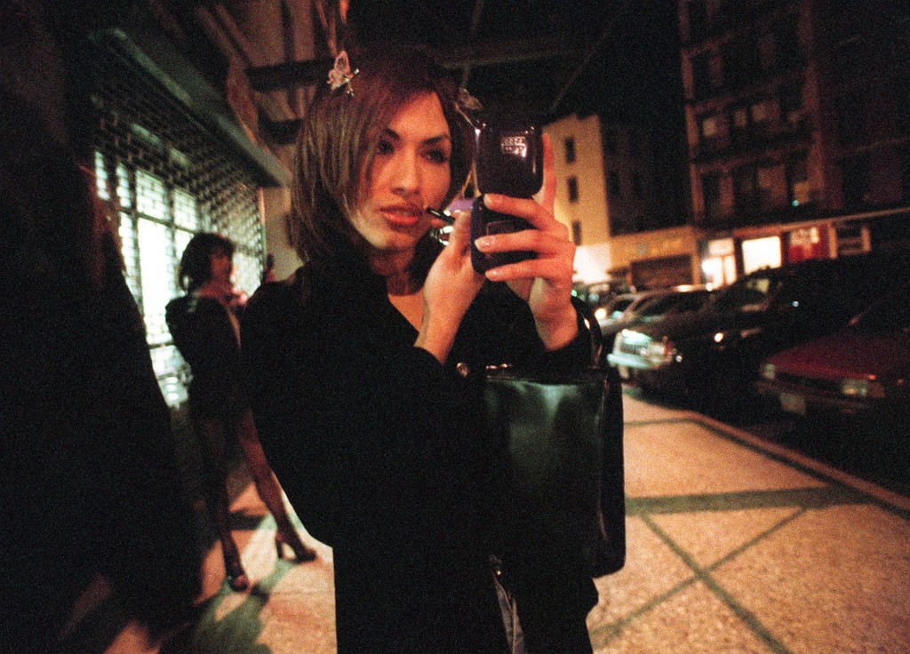 Christian Sosa reapplies her make-up on Little W 12th Street in New York Sunday morning, April 25, 1999, while other transgender prostitutes wait for clients in the background. Photo by Lynsey Addario