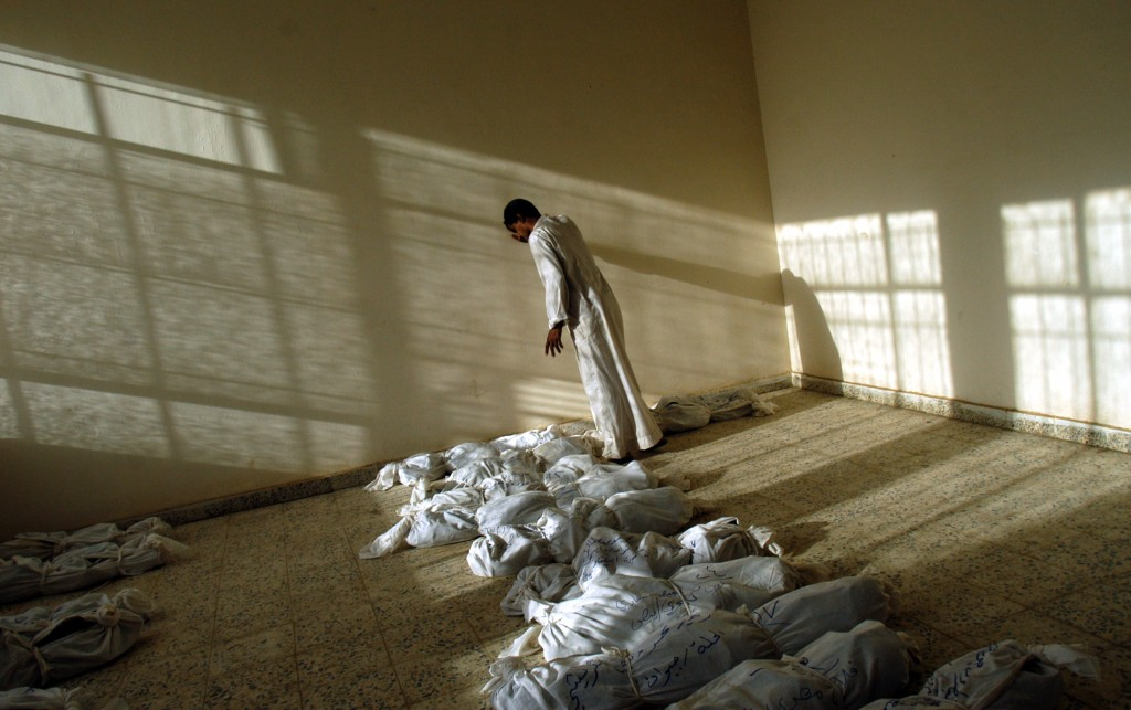 An Iraqi man leans against a wall as he walks along rows of remains of bodies discovered in a mass grave south of Baghdad, now laid out in a building in Iraq, May 29, 2003. After the fall of Saddam Hussain's regime in Iraq, thousands of bodies were pulled from mass grave sites around the country, evidence of the brutal, bloody regime of the former dictator. Photo by Lynsey Addario