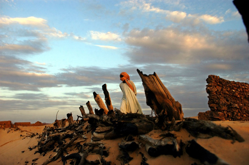 A Sudanese Liberation Army soldier walks through the remains of Hangala village on August 27, 2004, which was burned by Janjaweed several months earlier. Thousands of Darfourians fled their villages in search of shelter in the mountains or in neighboring Chad because of continuing attacks on civilians. Photo by Lynsey Addario