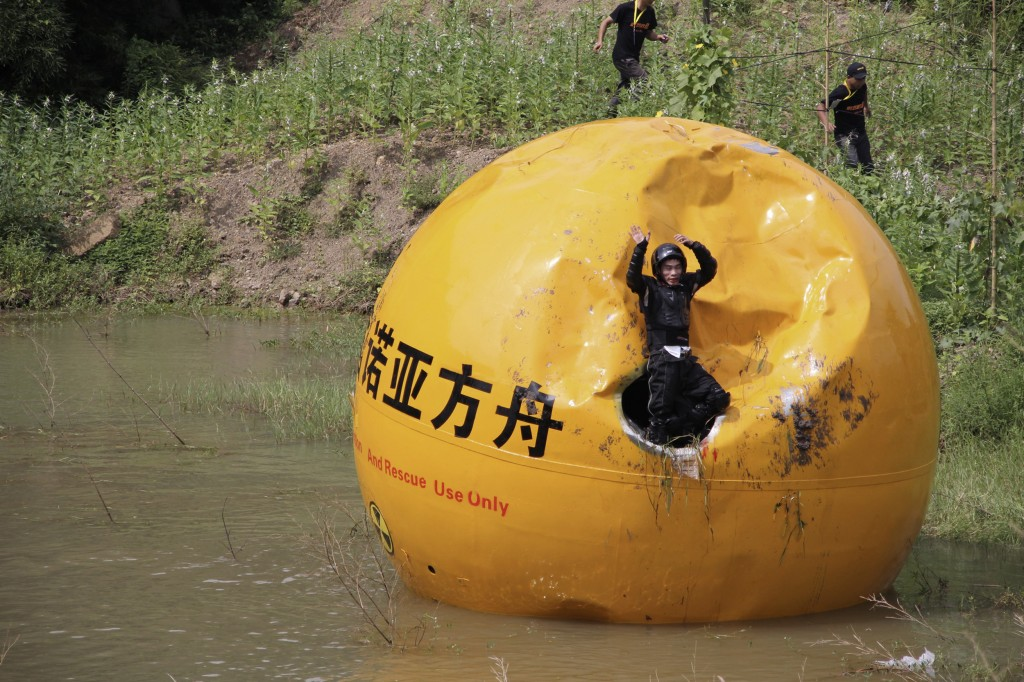 Chinese inventor Yang Zongfu emerges from his six-ton ball container named Noah's Ark of China after conducting tests on the vessel in Yiwu, Zhejiang province. Chinese media reported that Yang spent two years and more than $235,000 to build this 16-foot diameter bunker that is big enough to contain a three-person family and enough food to feed them for 10 months. Photo by Reuters/China Daily.