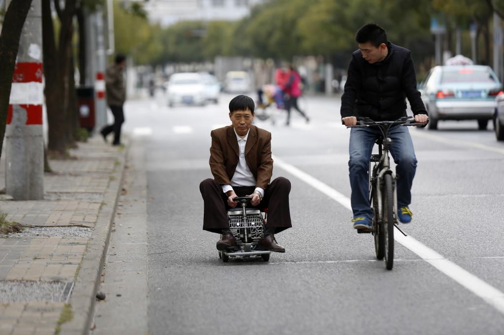 Xu Zhiyun, 60, drives the pocket-sized vehicle along a street in Shanghai, a vehicle that he invented after two years of work. The vehicle is about the size of a briefcase and contains an engine and five gears. Photos by Reuters/Aly Song.