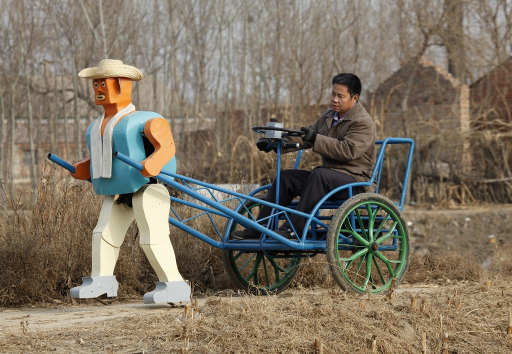 A walking robot pulls the rickshaw of farmer and amateur inventor Wu Yulu near his village outside Beijing. Wu began building robots nearly three decades ago, using items such as wire, scrap metal and debris that he found discarded in the trash.  Photo by Reinhard Krause.