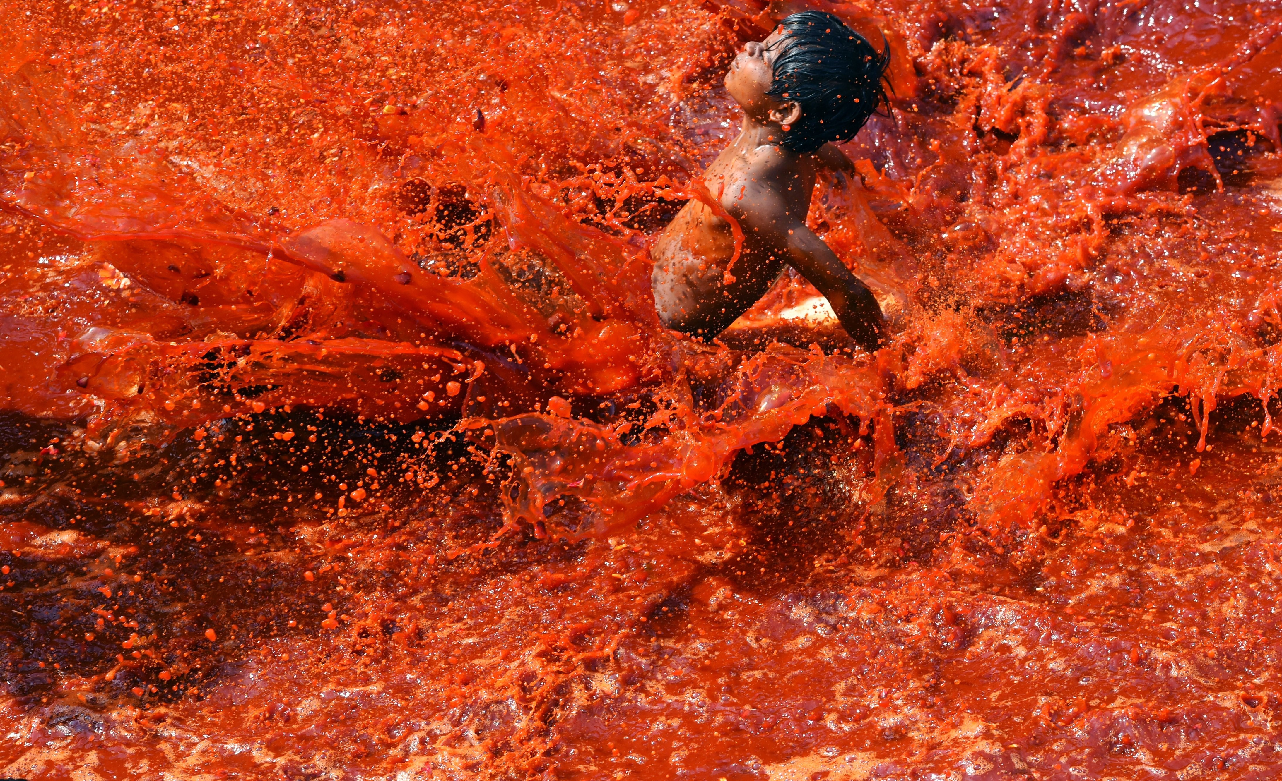 An Indian boy slides in the remnant water left after a large crowd of men and women participated in the Dadjee ka Huranga festivities in the north Indian town of Baldeo on March 7, 2015. Photo by ROBERTO SCHMIDT/AFP/Getty Images.