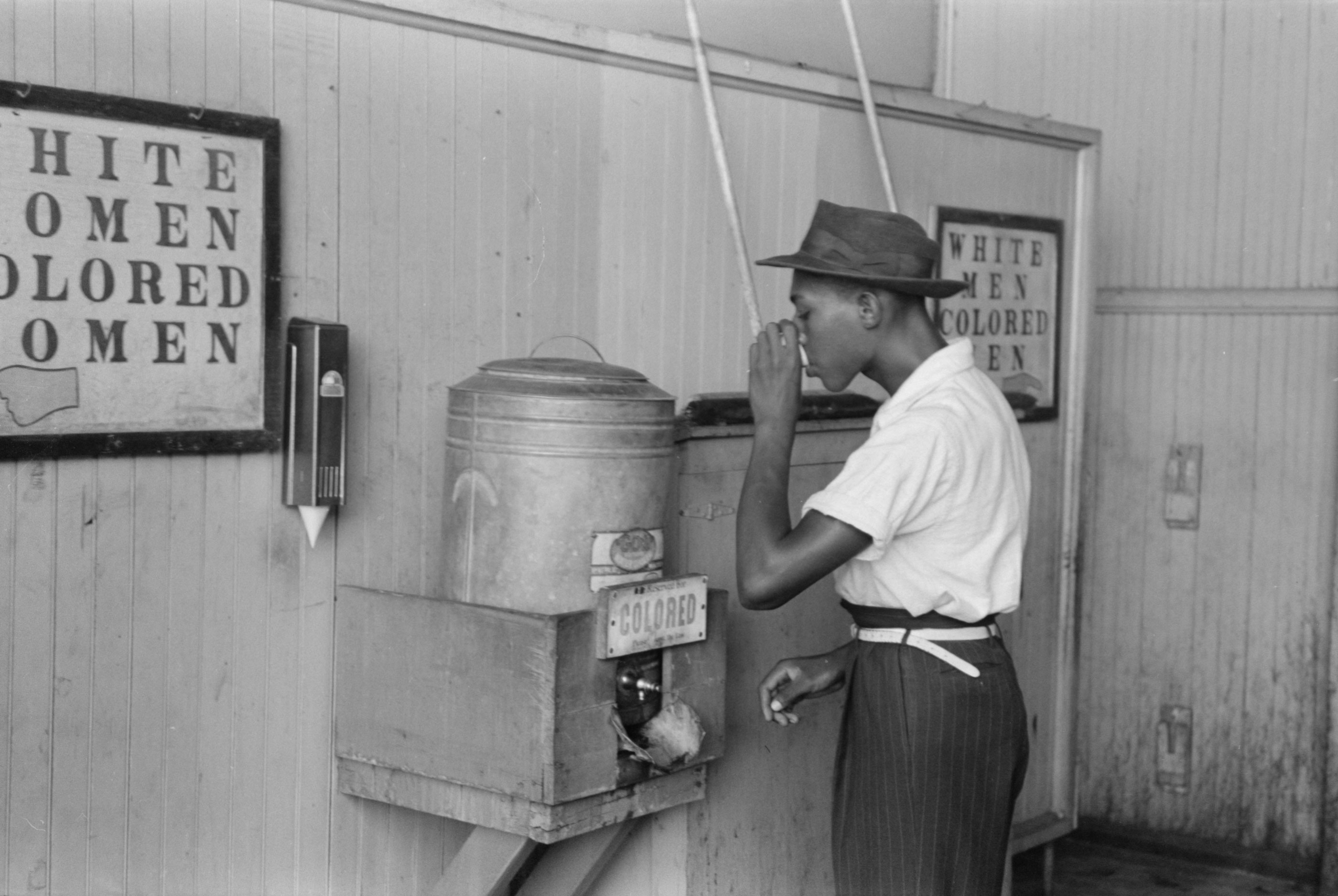 """A man drinks at a """"colored"""" water cooler in a streetcar terminal in Oklahoma City, in this July 1939 photograph courtesy of the Library of Congress. Photo by REUTERS/Library of Congress/Handout via Reuters."""