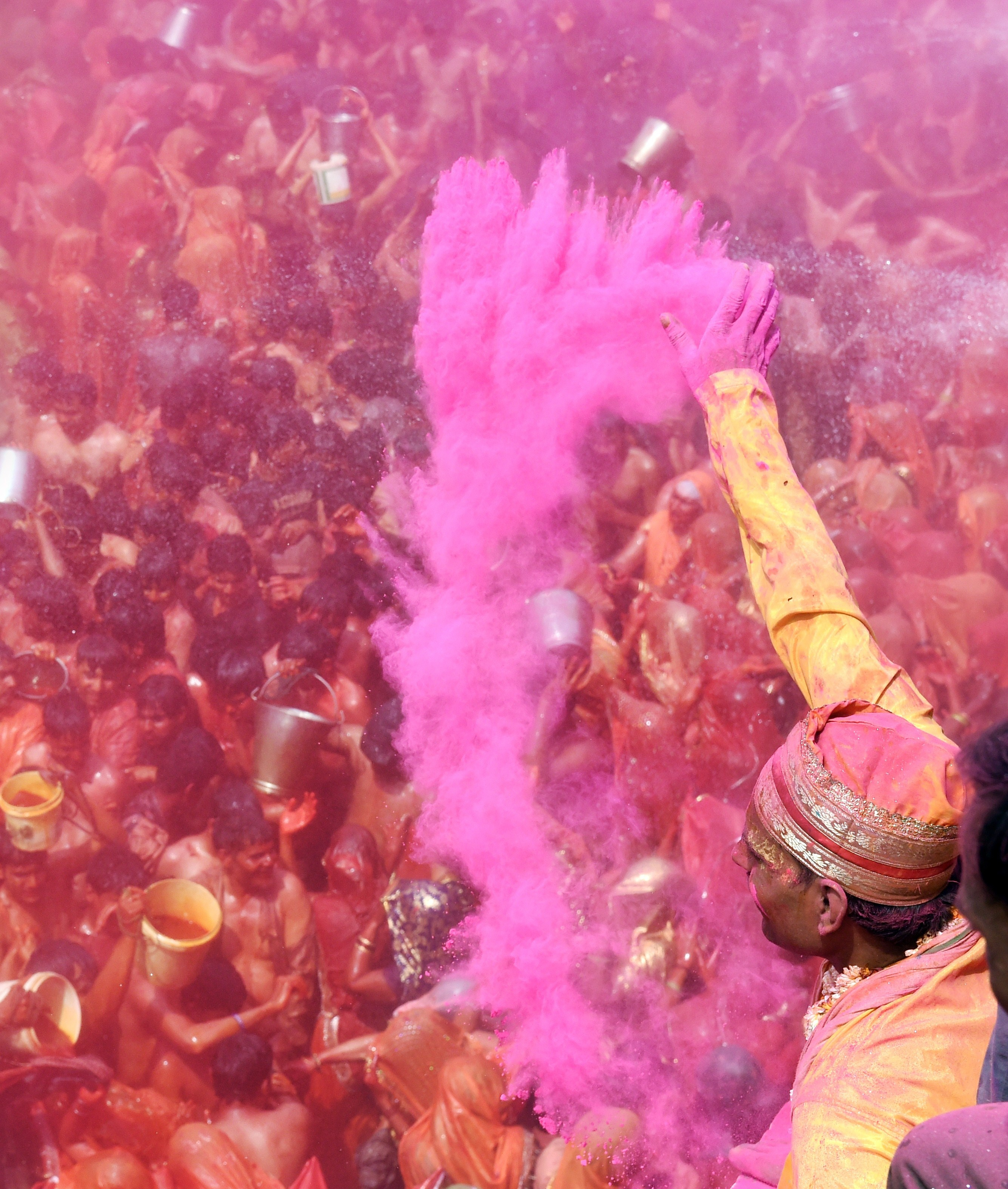 An Indian man throws colored powder on a crowd of revelers during the Dadjee ka Huranga festivities in the north Indian town of Baldeo on March 7, 2015. Photo by ROBERTO SCHMIDT/AFP/Getty Images.