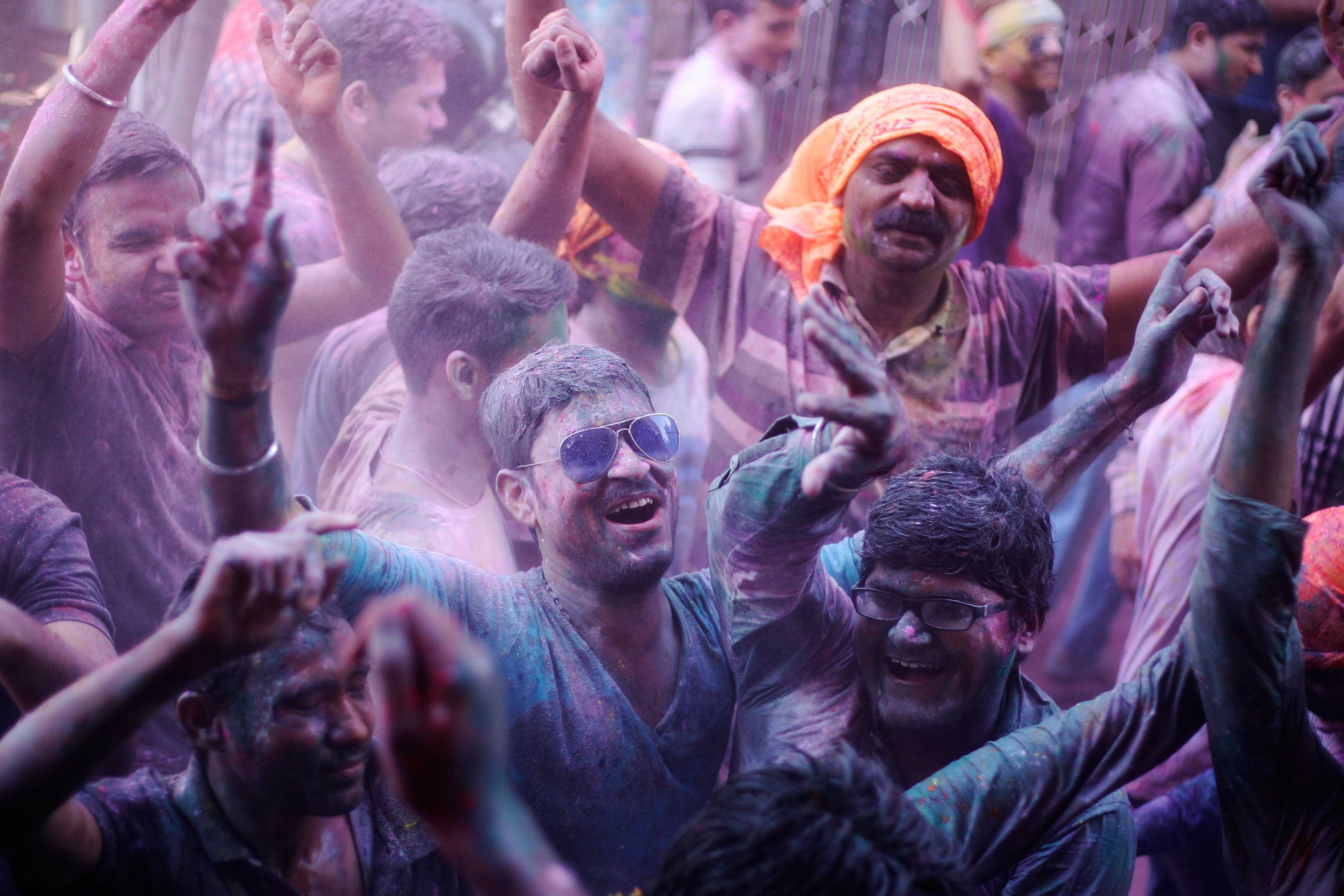 People smeared in colours celebrate Holi on a street outside the Bankey Bihari temple, on March 6, 2015 in Vrindavan, India. Photo by Burhaan Kinu/Hindustan Times via Getty Images.