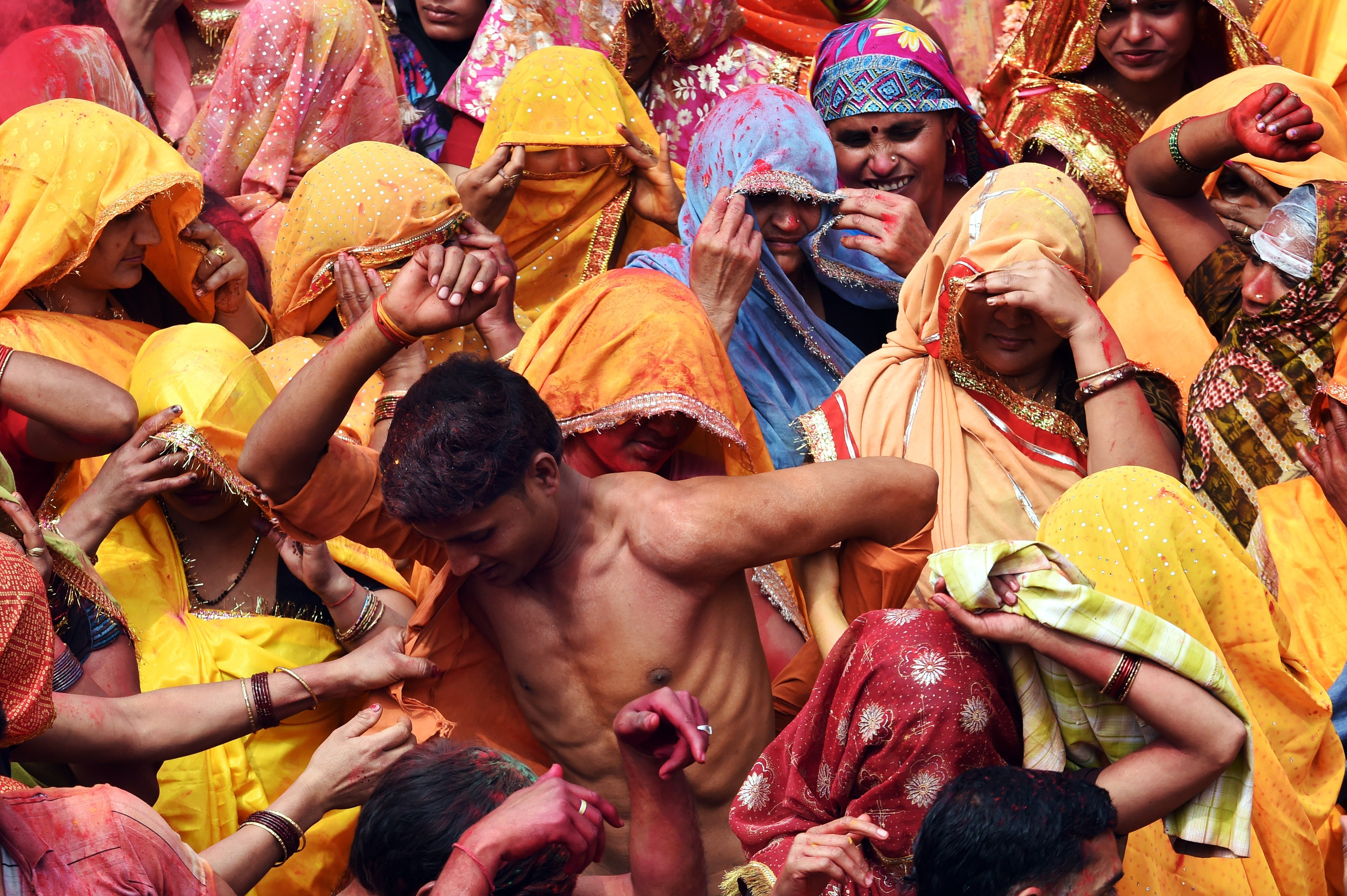 An Indian man is stripped of his shirt as he is surrounded by women at the beginning of the Dadjee ka Huranga festivities in the north Indian town of Baldeo on March 7, 2015. Photo by ROBERTO SCHMIDT/AFP/Getty Images.