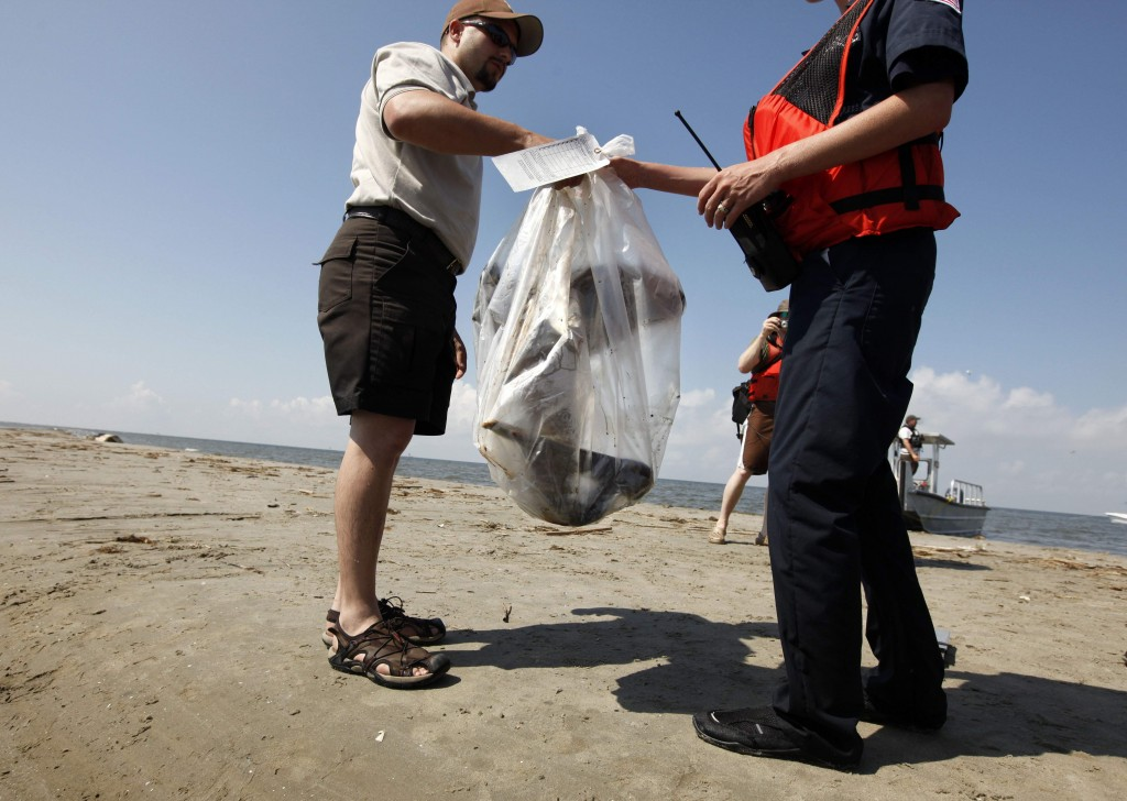 Pelican Handoff U.S. Fish and Wildlife officer Raul Sanchez hands off a dead oil-covered pelican to an unidentified Coast Guard personnel after bagging and tagging it as evidence on North Breton Island, La., Thursday, May 20, 2010. (AP Photo/Gerald Herbert)