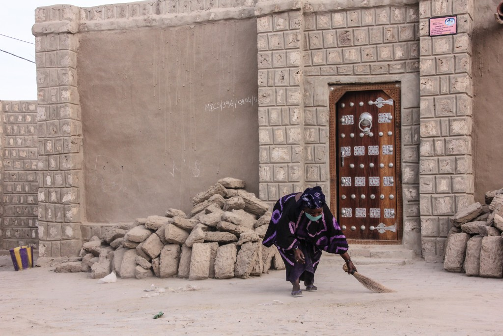 A woman in Timbuktu sweeps the sand away from the front of her doorstep. Because Timbuktu sits on the edge of the vast Sahara desert, sand encroaches everywhere. Photo by Molly Raskin