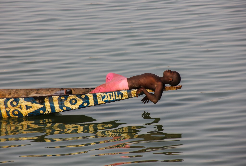 A boy floats down the Niger River on a pirogue, a traditional wooden boat used for transport and fishing. Plagued by frequent droughts, Mali survives largely because of its access to the Niger, the third longest river in Africa. Photo by Molly Raskin