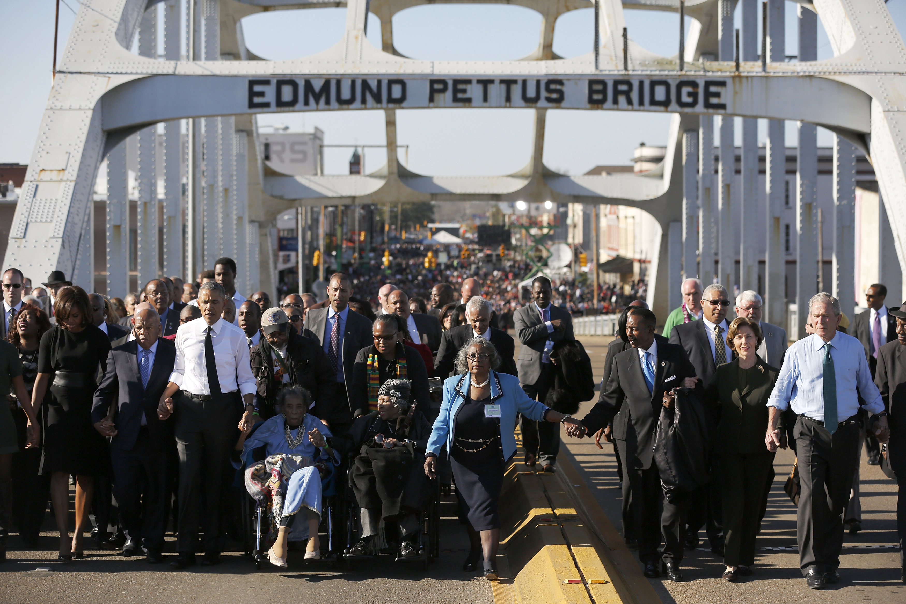 U.S. President Barack Obama (3rd L) participates in a march across the Edmund Pettus Bridge in Selma, Alabama, March 7, 2015. Also pictured are first lady Michelle Obama (L), U.S. Representative John Lewis (D-GA) (2nd L), former first lady Laura Bush (2nd R) and former president George W. Bush (R). The event comes on the 50th anniversary of the 'Bloody Sunday' march at the bridge, where police and state troopers beat and used tear gas against peaceful marchers who were advocating against racial discrimination at the voting booth.  REUTERS/Jonathan Ernst    (UNITED STATES - Tags: POLITICS ANNIVERSARY SOCIETY TPX IMAGES OF THE DAY) - RTR4SGKC