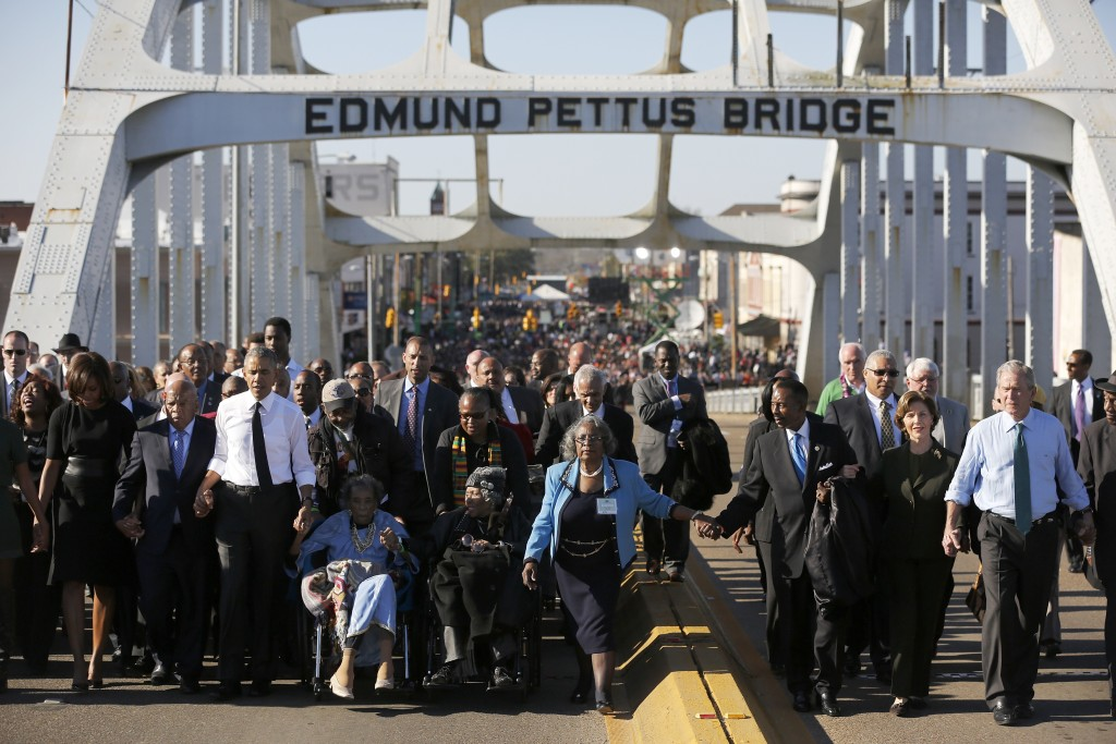 President Barack Obama crosses the Edmund Pettus Bridge with first lady Michelle Obama, Congressman John Lewis, former first lady Laura Bush and former president George W. Bush. Photo by Jonathan Ernst/Reuters