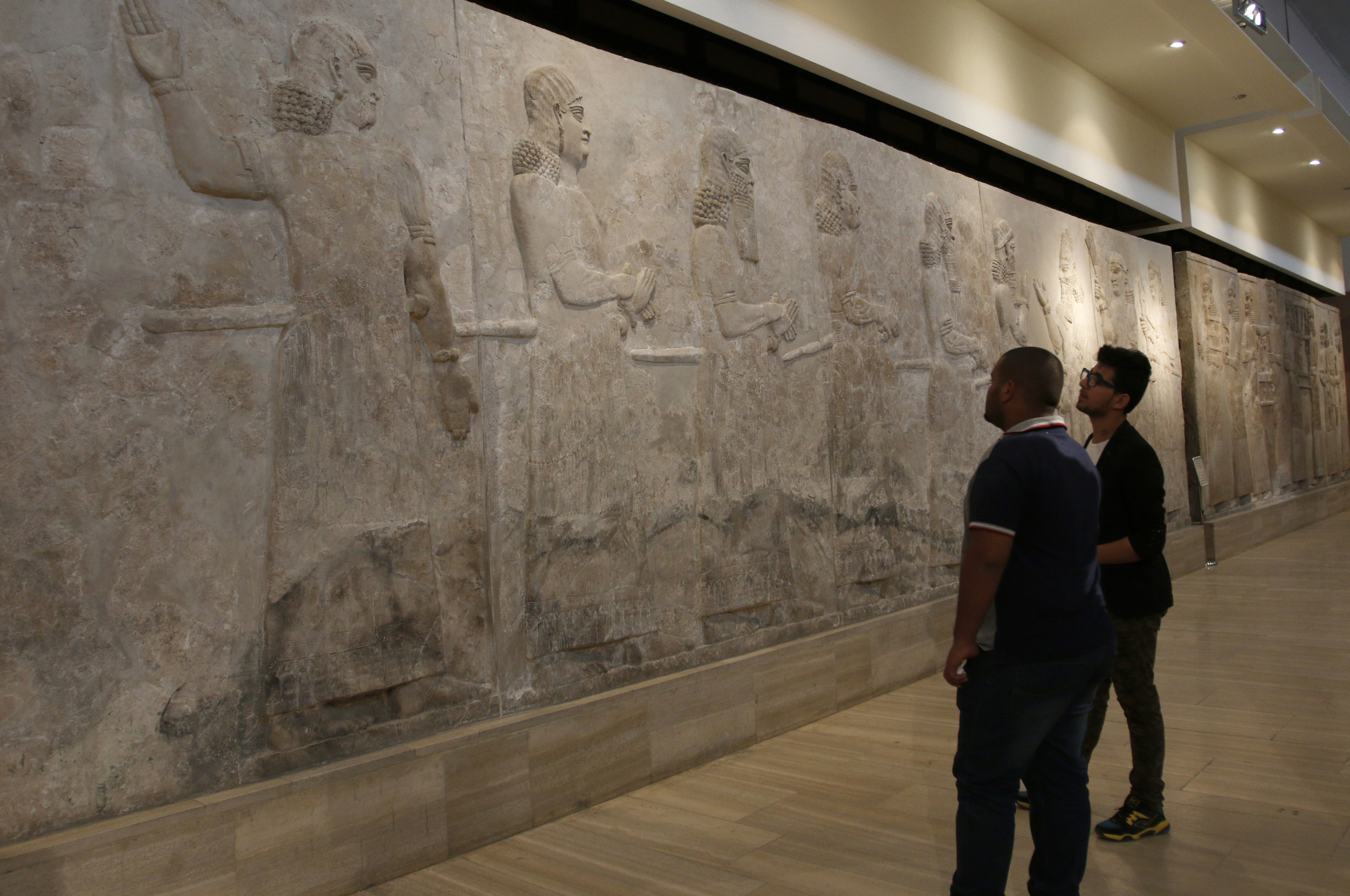 Visitors look at Assyrian mural sculptures at the Iraqi National Museum in Baghdad, March 8, 2015. Islamic State militants have desecrated Assyrian relics and ancient sites. Photo by Khalid al-Mousily/Reuters