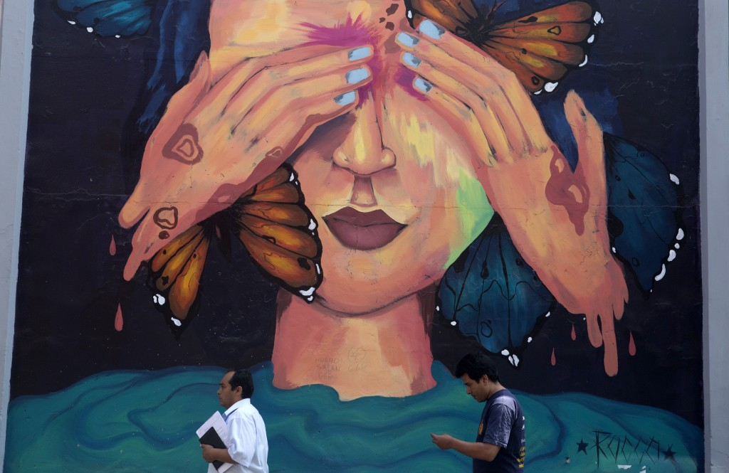 At Pachitea street in downtown Lima on Mar. 12, 2015, people walk past a mural.  Credit: Mariana Bazo/  REUTERS