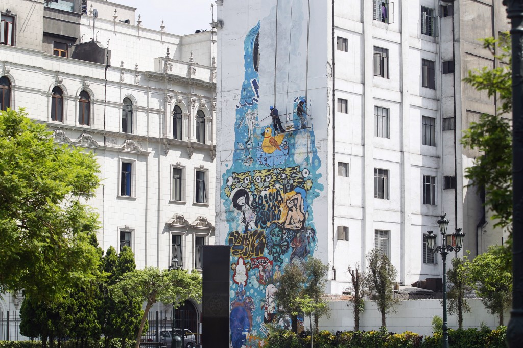 City hall workers paint over a mural at the Plaza de la Democracia in downtown Lima on Mar. 14, 2015. Credit: Enrique Castro-Mendivil/REUTERS