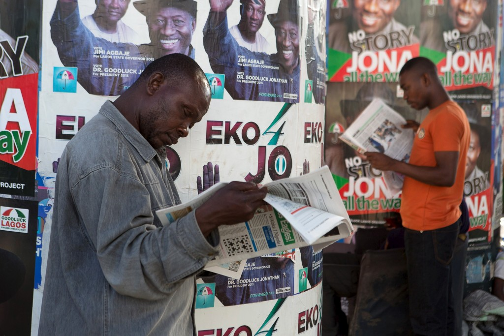 Men read newspapers in front of electoral campaign posters in Lagos, Nigeria, on March 30. Photo by Joe Penney/Reuters