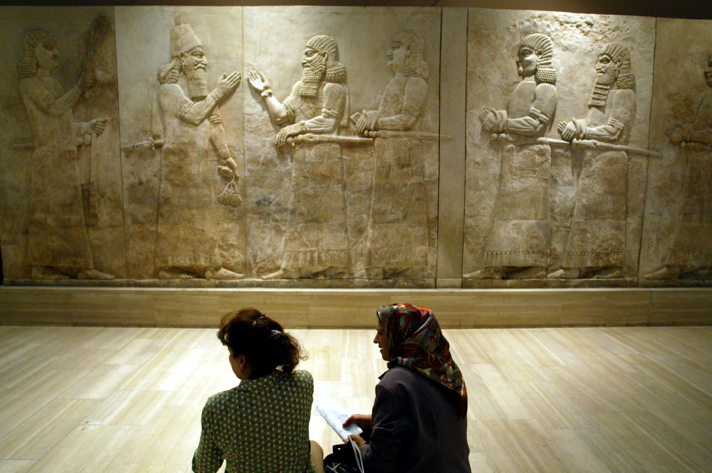 Two Iraqi women talk in front of Assyrian mural sculptures July 3, 2003 as the Baghdad museum briefly re-opened to display ancient Nimrud treasures. One of the most significant archaeological finds of the 20th century, the Nimrud treasures were destroyed by Islamic State militants, the Iraqi ministry announced Thursday. Photo by Radu Sigheti/Reuters