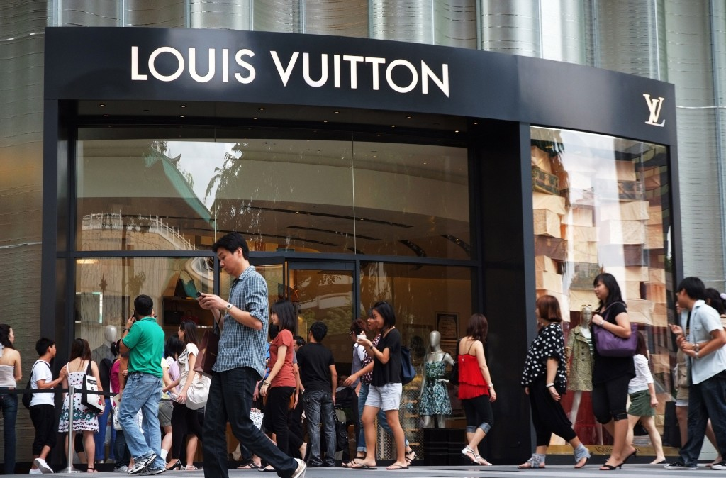 Shoppers walk past the luxury Louis Vuitton store during Christmas Eve in central Singapore in 2010. Photo by Kevin Lam/Reuters