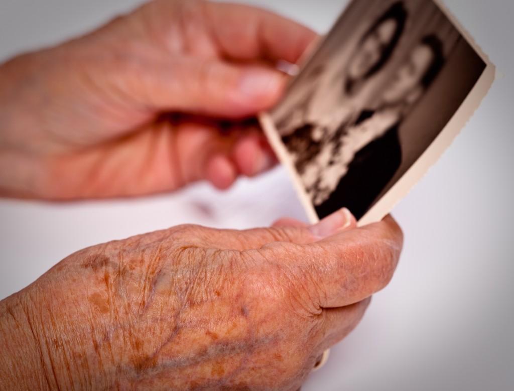 Elderly hands holding photograph