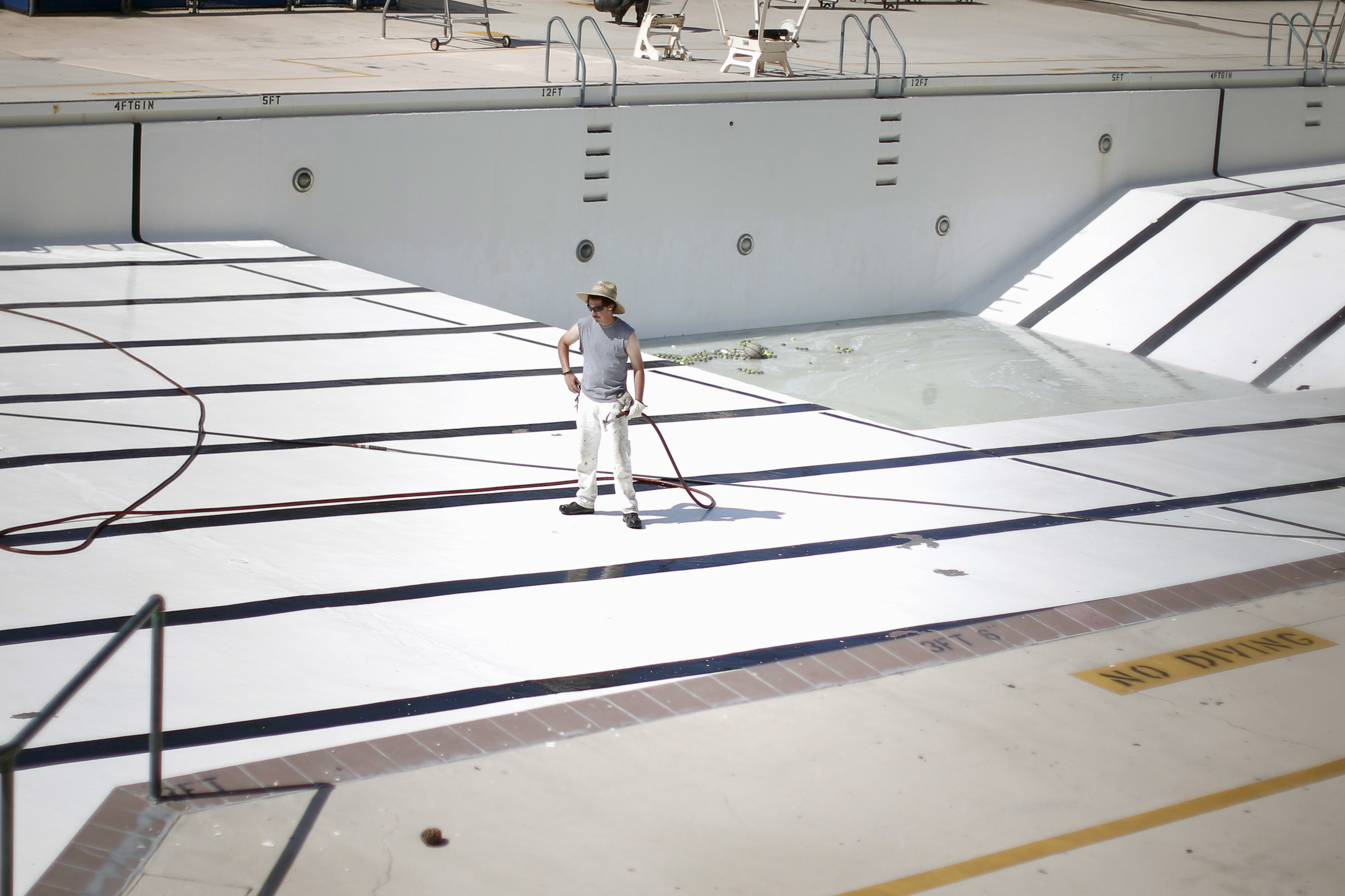 A man stands in an empty public swimming pool in Burbank, Los Angeles, California March 19, 2015. Photo by Lucy Nicholson/Reuters