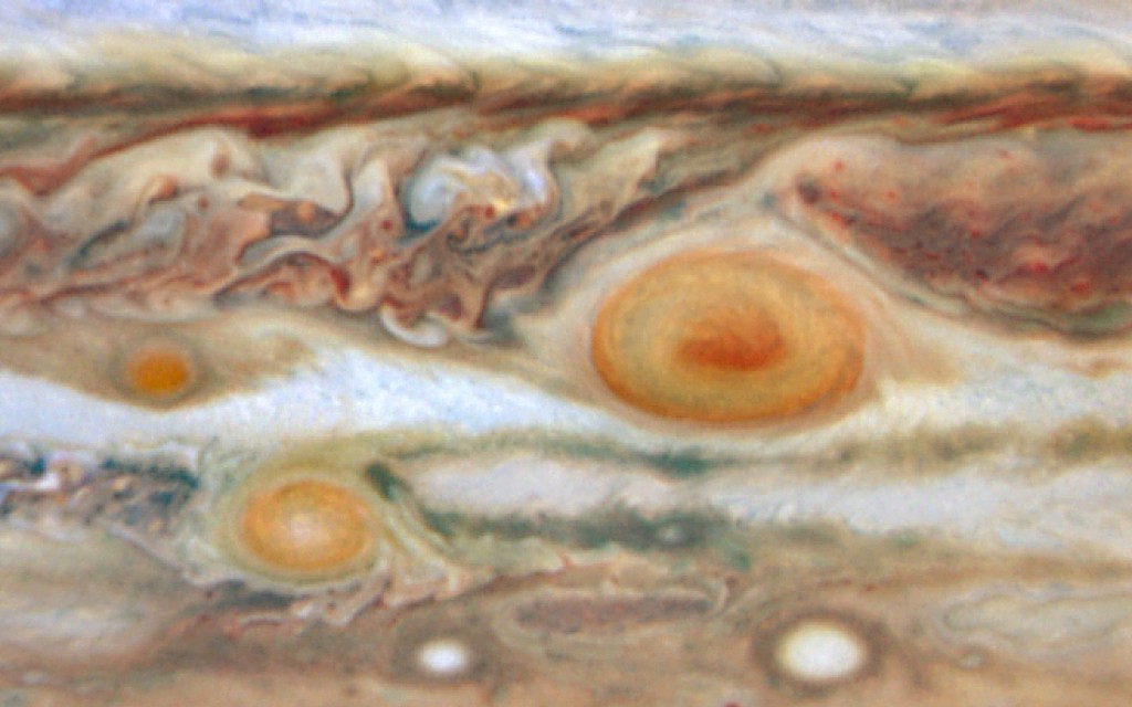 This May 22, 2008, image reveals a third red spot alongside its cousins -- the Great Red Spot and Red Spot Jr.  The new red spot was previously a white oval-shaped storm. The change to a red color indicates its swirling storm clouds are rising to heights like the clouds of the Great Red Spot. width=