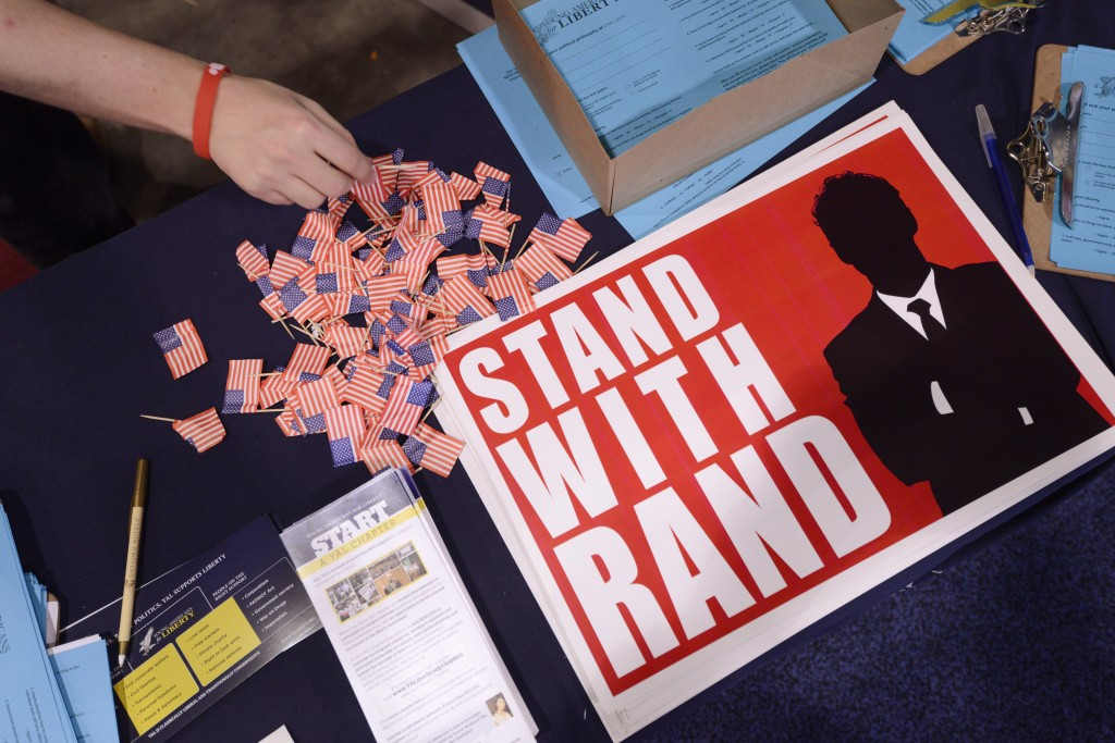 A guest reaches for a flag pin at the Senator Rand Paul (R-KY) booth at the Conservative Political Action Conference (CPAC) in National Harbor, Maryland, February 28, 2015. CPAC closes after three days where thousands of conservative activists, Republicans and Tea Party Patriots gathered to hear politicians, presidential hopefuls, and business leaders speak, lobby and network for a conservative agenda, ahead of the presidential election in 2016. Photo by Mike Theiler/Reuters