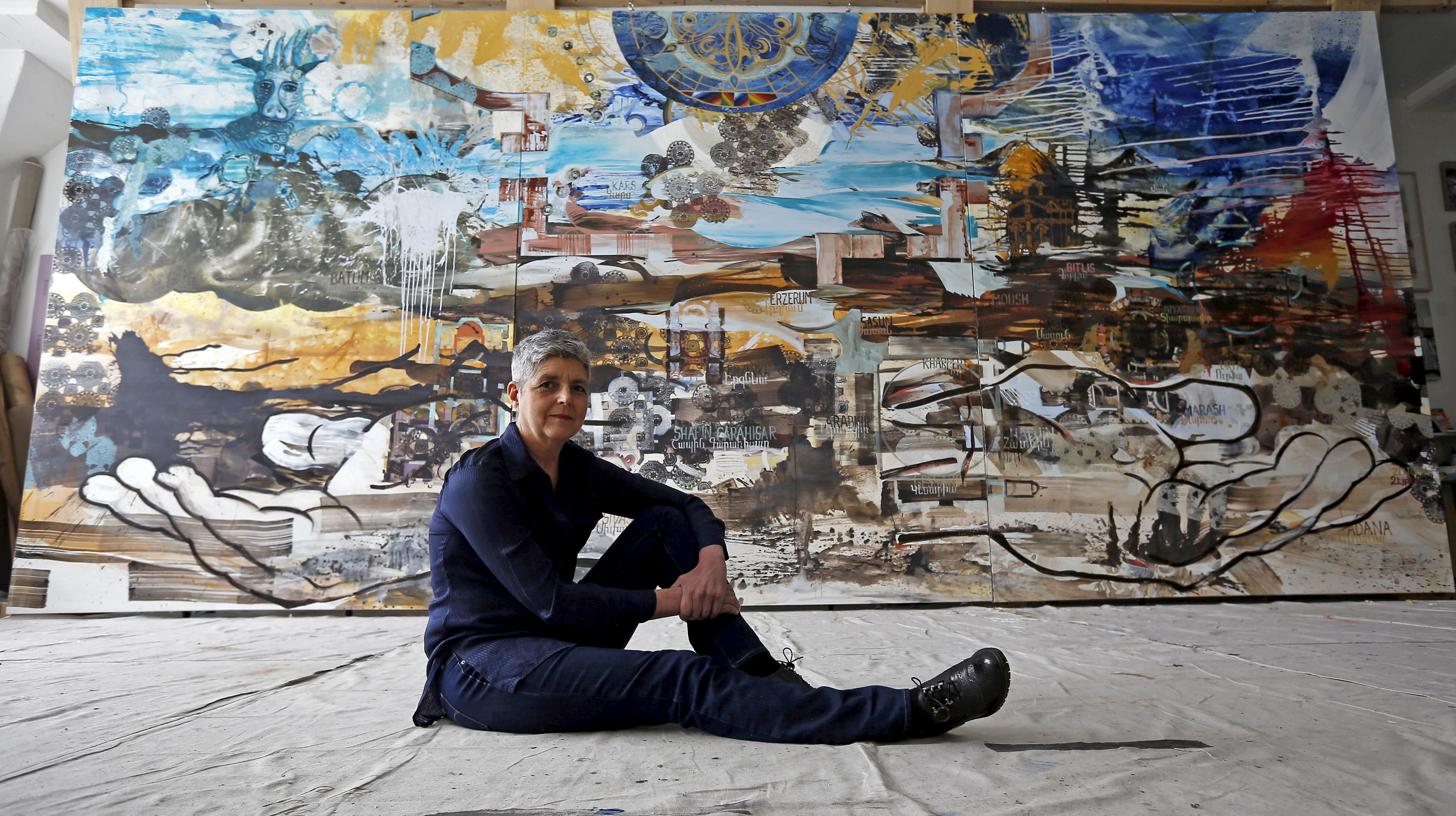 "Artist Jackie Kazarian poses in front of her mural ""Project 1915"" depicting Armenia's history and a culture ""that has that has survived for 3,000 years,"" she says. Her work will be on display at Chicago's Mana Contemporary until May 29, 2015. Photo by Jim Young/Reuters"