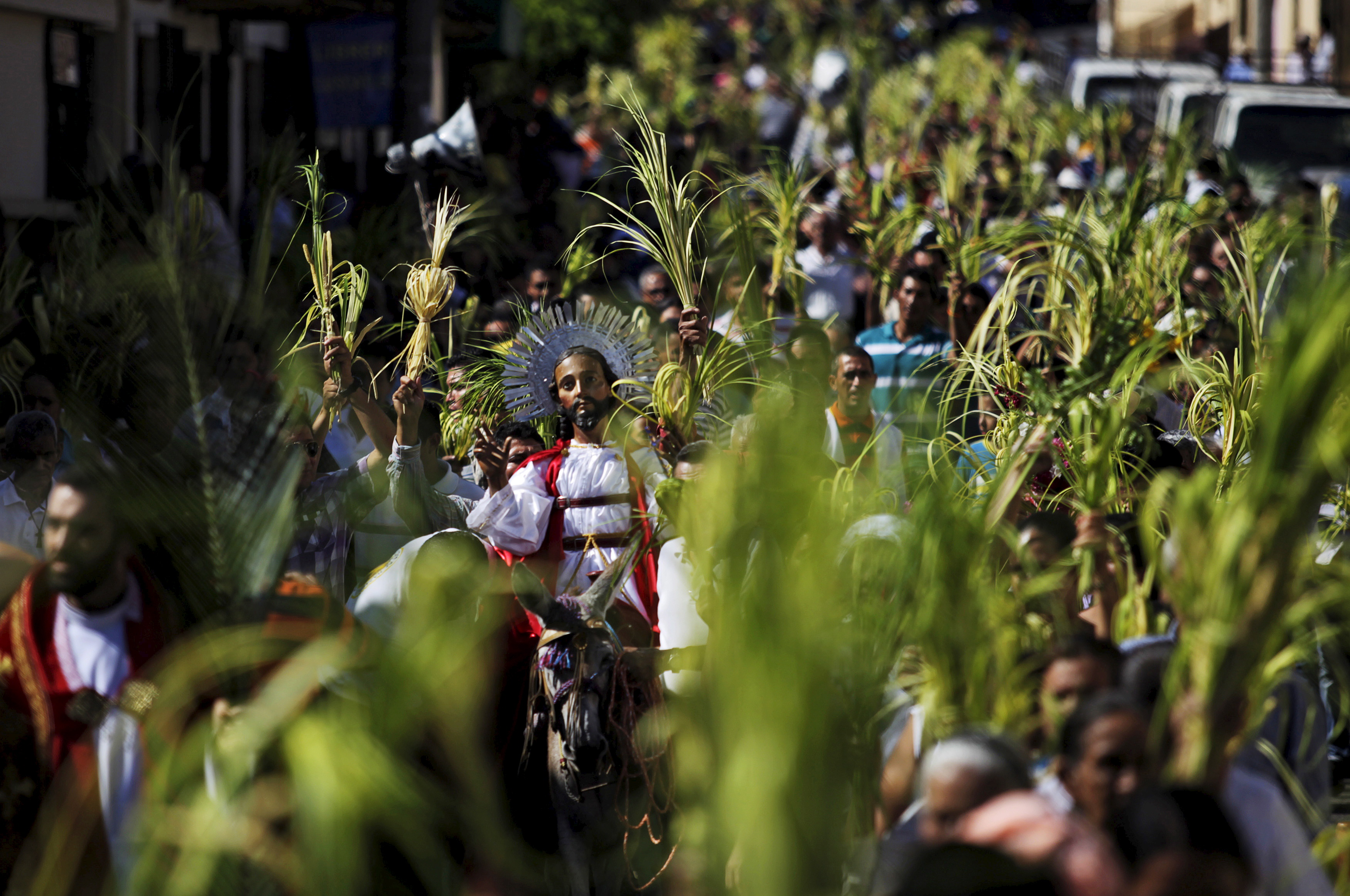 Catholics participate in the Palm Sunday procession in Suchitoto March 29, 2015. Palm Sunday commemorates Jesus Christ's triumphant entry into Jerusalem on the back of a donkey and marks the start of Holy Week.   REUTERS/Jose Cabezas