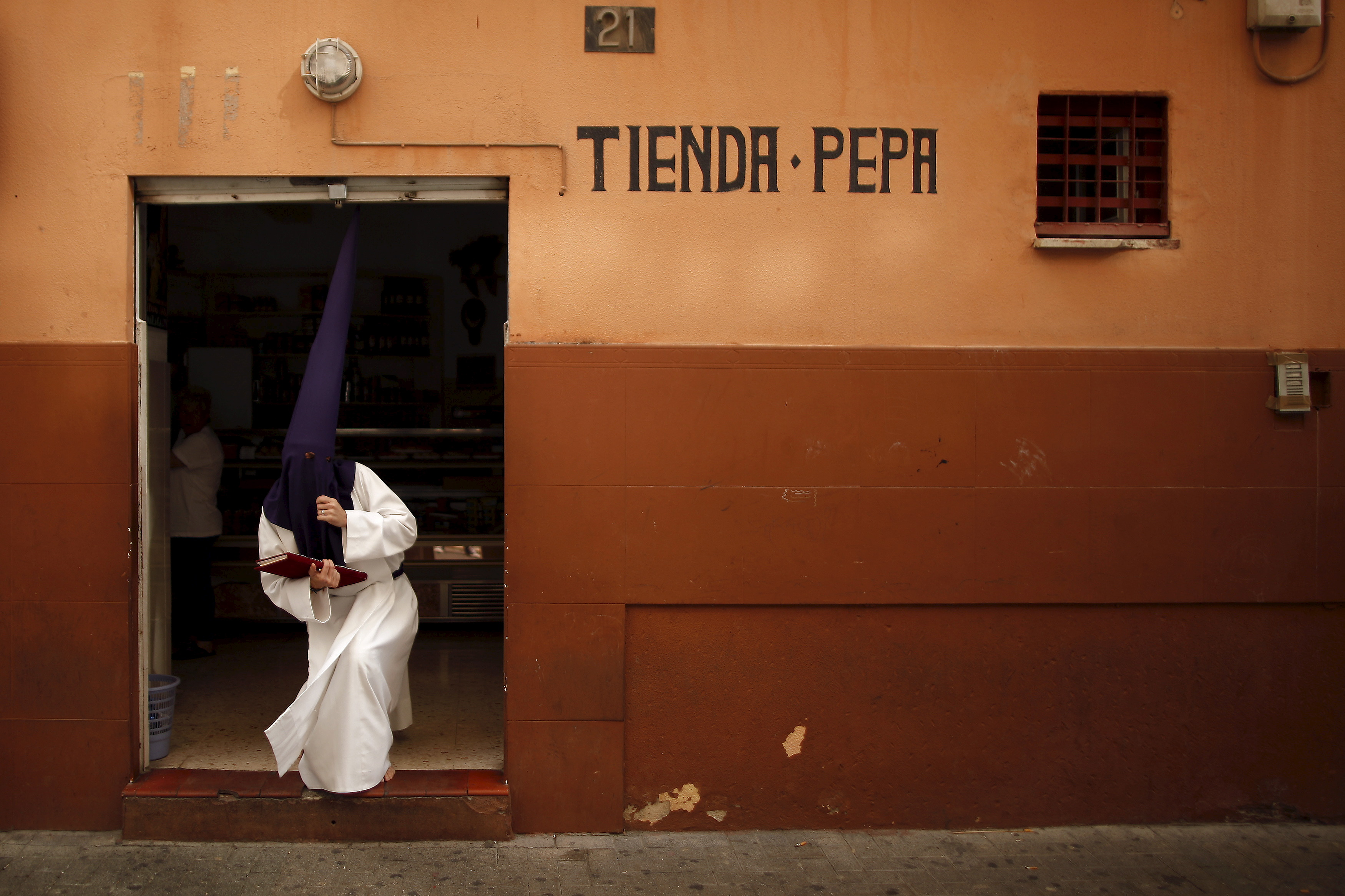 "A penitent leaves a food shop before he takes part in the ""Huerto"" brotherhood in a Palm Sunday procession at the start of Holy Week in Malaga,Spain during Holy Week, drawing thousands of visitors. REUTERS/Jon Nazca"