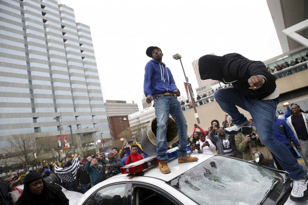 "Protesters jump on a police car at a rally to protest the death of Freddie Gray who died following an arrest in Baltimore, Maryland April 25, 2015. More than 1,000 demonstrators chanting ""shut it down"" marched through Baltimore on Saturday to protest the death of a black man who died after being taken into police custody. REUTERS/Shannon Stapleton       TPX IMAGES OF THE DAY      - RTX1AAHE"