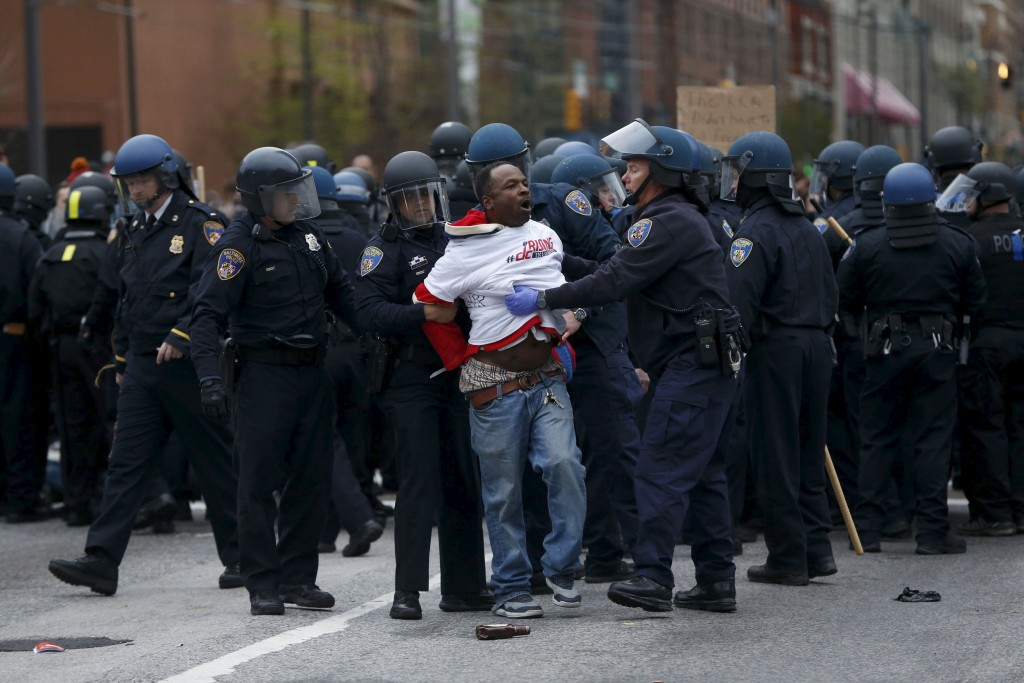 "Police detain a protester at a rally to protest the death of Freddie Gray who died following an arrest in Baltimore, Maryland April 25, 2015. More than 1,000 demonstrators chanting ""shut it down"" marched through Baltimore on Saturday to protest the death of a black man who died after being taken into police custody. REUTERS/Shannon Stapleton"