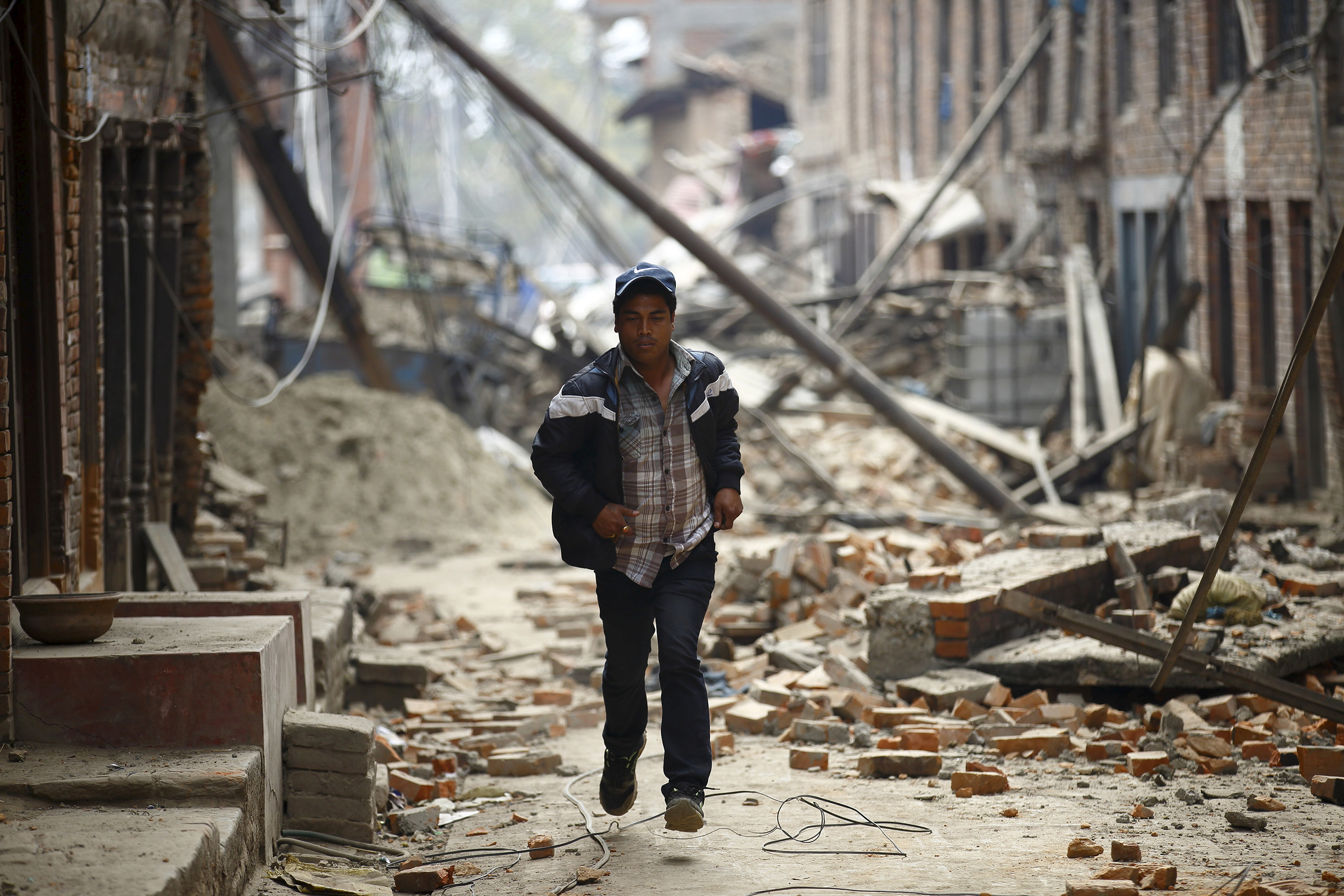 A man runs past damaged houses as aftershocks of an earthquake are felt a day after the earthquake in Bhaktapur, Nepal April 26, 2015. Photo by Navesh Chitrakar/REUTERS.