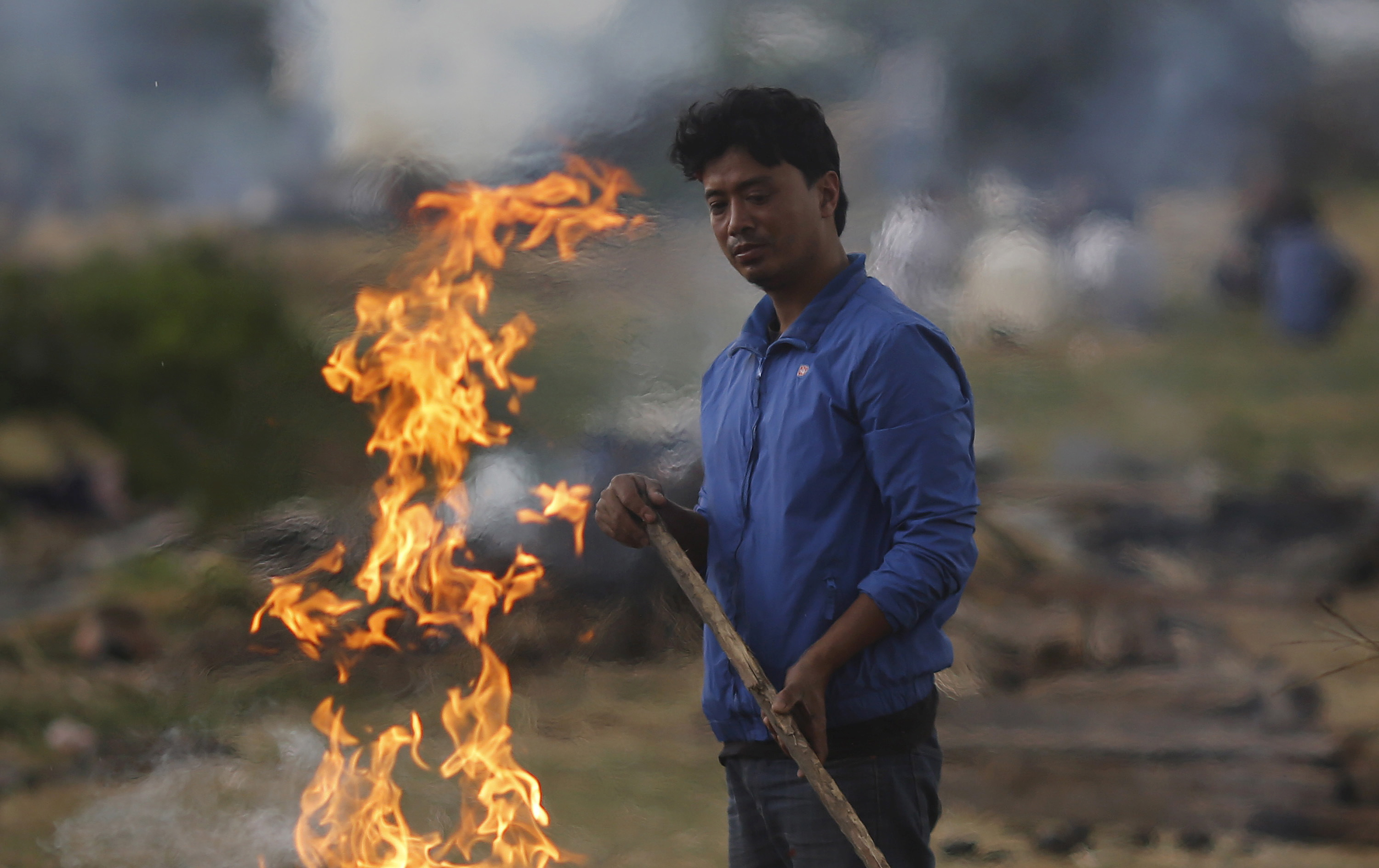 A man stands next to the burning pyre of a family member at a cremation ground after Saturday's earthquake in Bhaktapur, Nepal on Monday. Photo by Adnan Abidi/Reuters