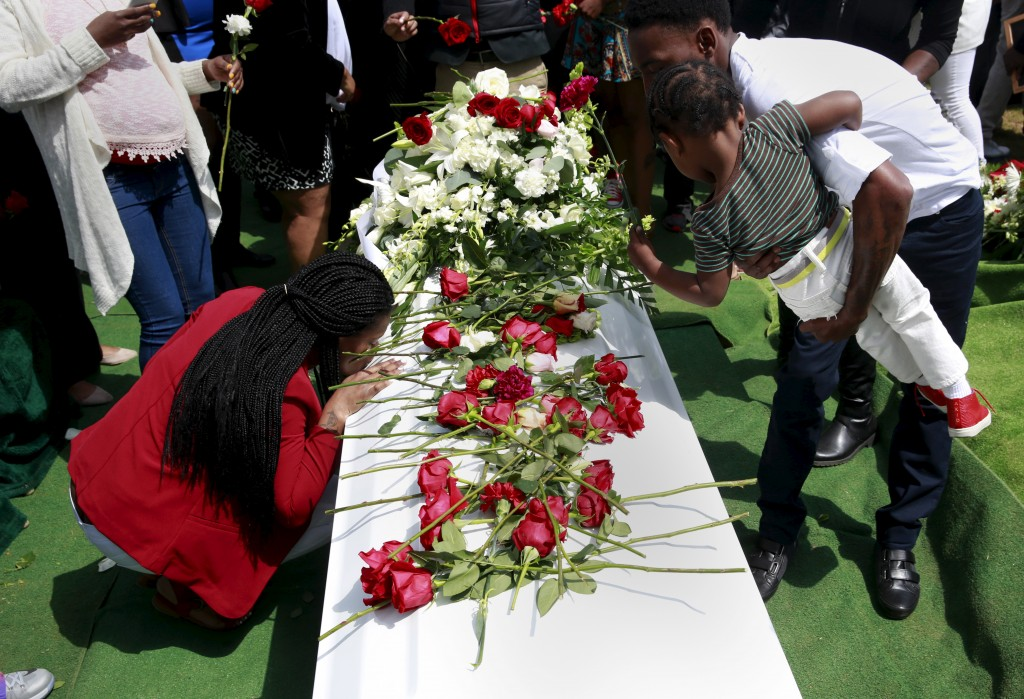 A woman kisses the casket of Freddie Gray, who died following an arrest by the Baltimore police department, at his burial at Woodlawn Cemetery in Baltimore, Maryland on April 27, 2015. Photo by Shannon Stapleton/Reuters