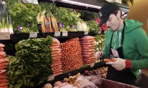 Whole Foods grocery store worker Tim Owen trims the tops of organic carrots in the produce section of the store in Ann Arbor, Michigan, March 8, 2012. Photo by Rebecca Cook/Reuters