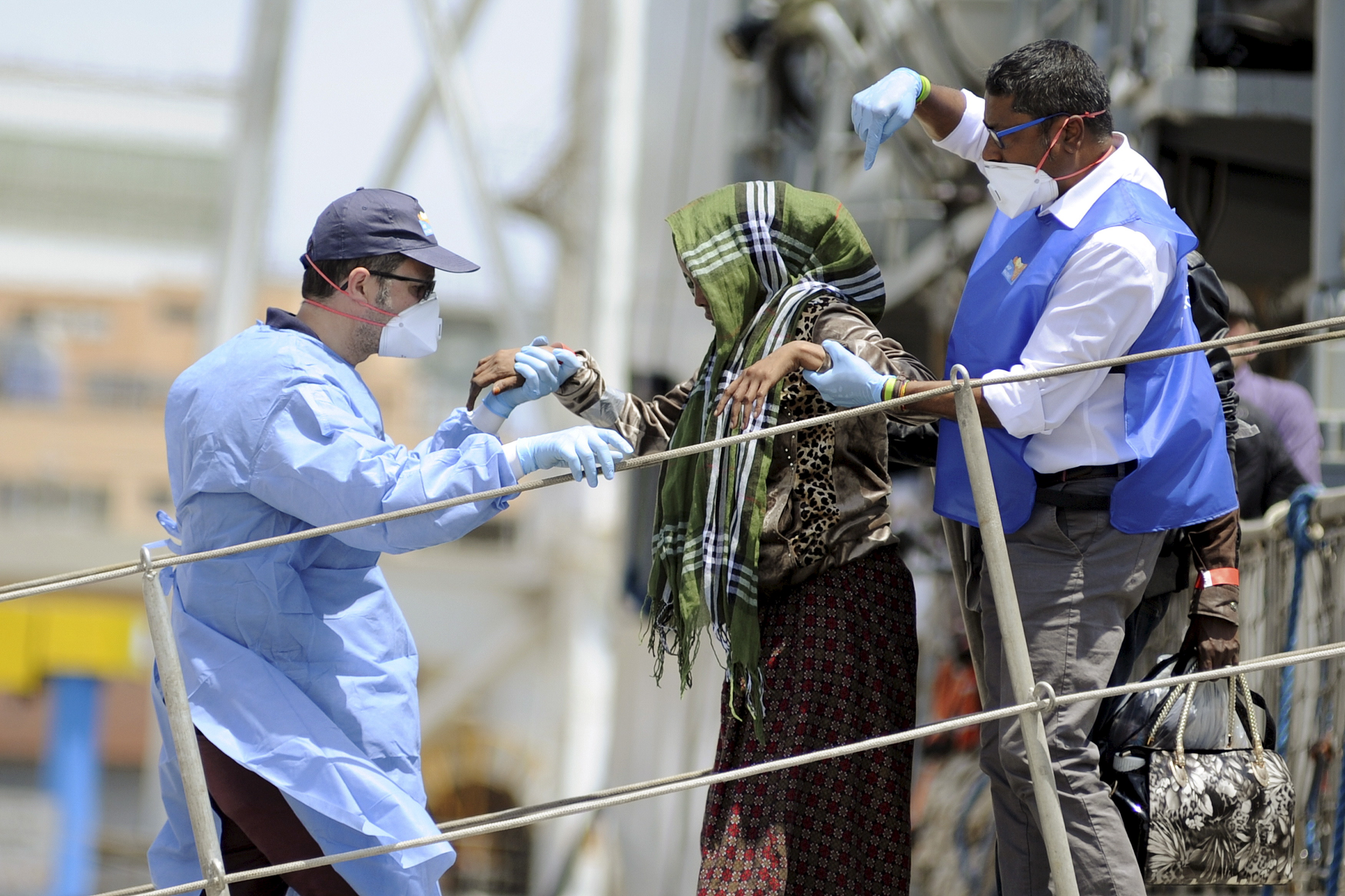 A woman is helped by medical staff as she disembarks from the Irish navy ship LE Eithne in the Sicilian harbour of Palermo, Italy, May 30, 2015. Photo by Guglielmo Mangiapane/Reuters