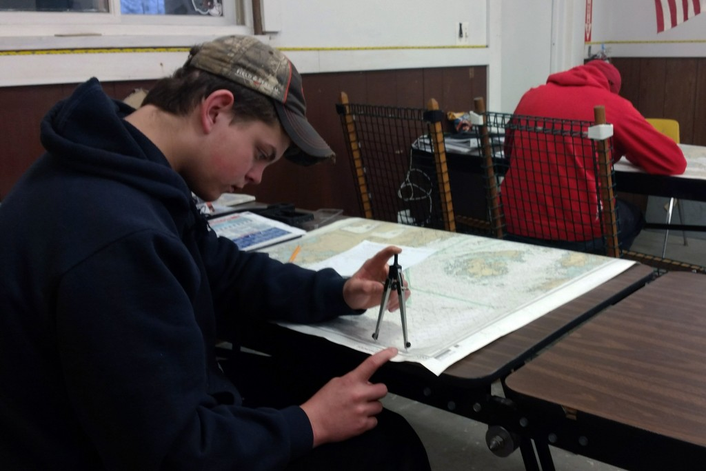 Elliot Nevells takes a test on navigation in his marine trades class. The Deer Isle-Stonington High School freshman says before he knew about the school's marine studies program, he thought he'd probably drop out of high school. (Photo: Sarah Butrymowicz/The Hechinger Report)