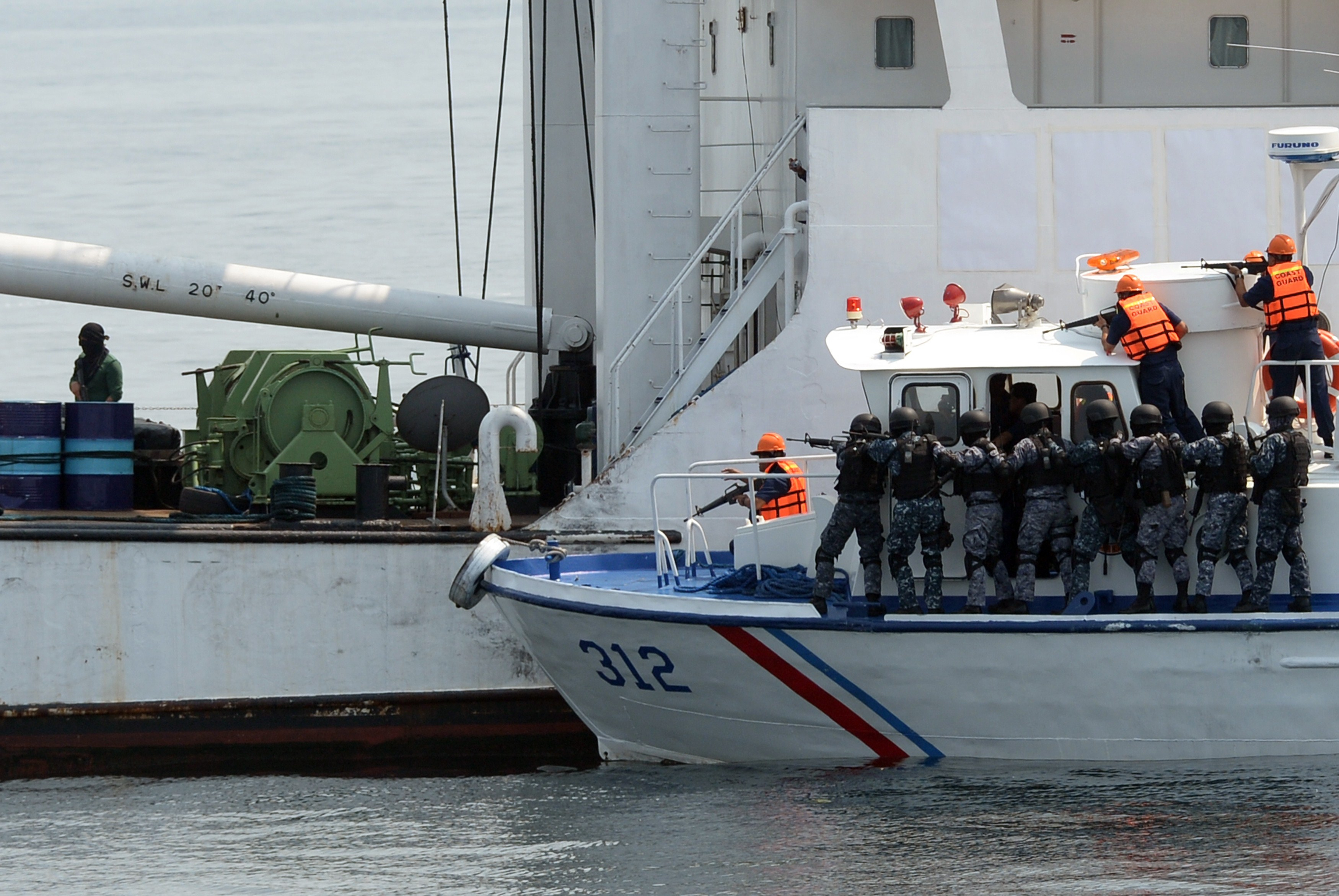 Philippine coastguard personnel prepare to board a ship during a simulation of a sea jacking scenario as part of the combined Philippine-Japan maritime exercise off Manila bay, in the mouth of South China sea on May 6, 2015. Photo by TED ALJIBE/AFP/Getty Images.