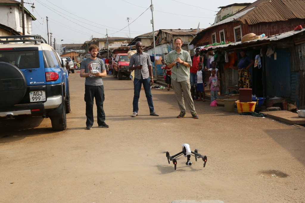A crowd gathers as cinematographer Cameron Hickey, flies a drone to capture video for the broadcast report.