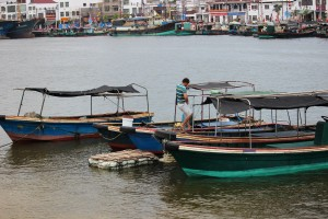 A fisherman stands aboard his boat docked at a village in Hainan Island, China. Photo by Tracy Wholf/NewsHour.