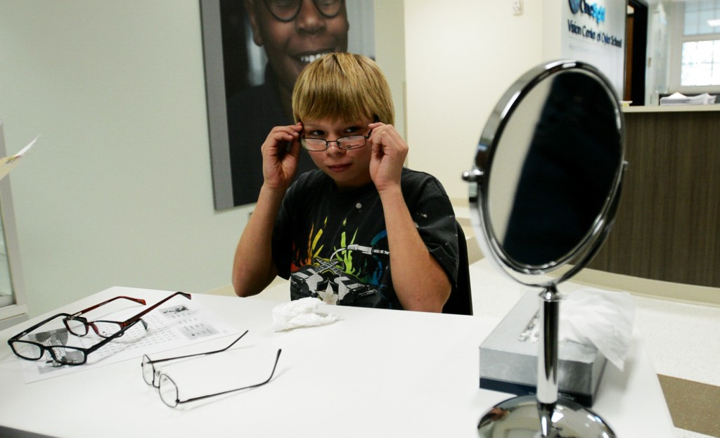 Timothy Drifmeyer, 13, tries on glasses at the OneSight Vision Center inside Oyler School. Photo by Stacy Doose