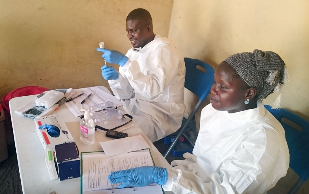 Health worker prep the Ebola vaccine in Guinea's capital, Conakry. Here, the outbreak continues with two new cases of Ebola being reported last week in the nation's largest city. Photo by World Health Organization.